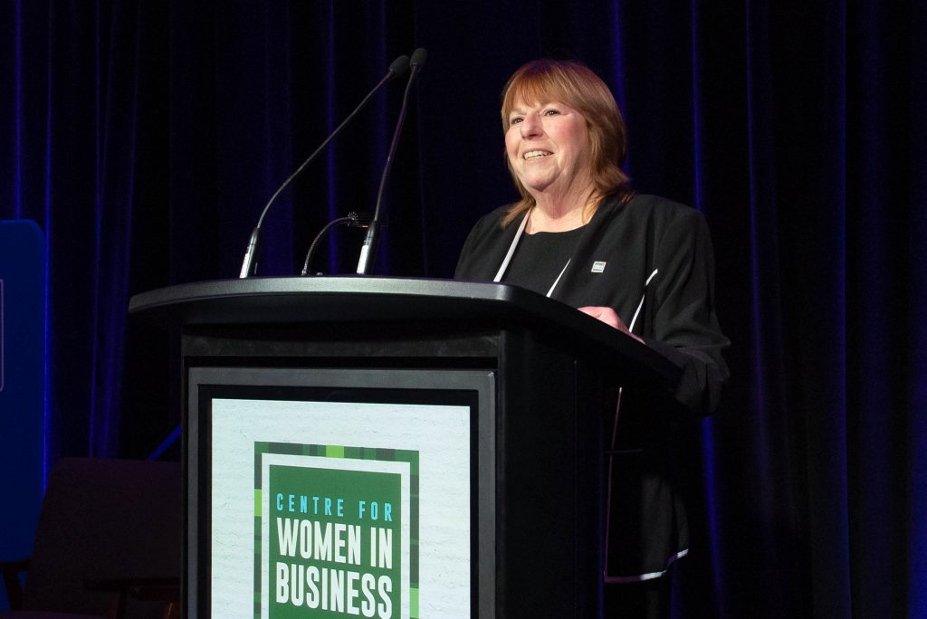Tanya Priske speaking into a microphone at the CWB International Women's Day event